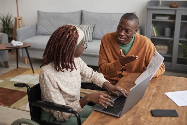 Портрет молодой афро-американской женщины в инвалидной коляске, работающей из дома с заботливым мужем, помогая ей скопировать пространство