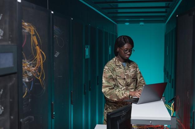 Портрет молодой афро-американской женщины в военной форме, использующей компьютер при настройке сети в серверной комнате, копией пространства