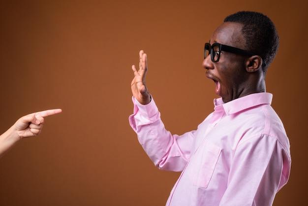 Портрет молодого африканского бизнесмена против коричневой стены