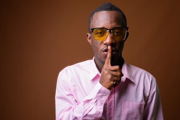 茶色の壁に対する若いアフリカの実業家の肖像画