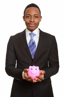 Портрет молодого африканского бизнесмена, держащего копилку