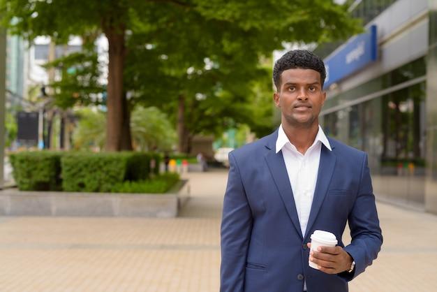 街の屋外でコーヒーカップをテイクアウト保持している若いアフリカの実業家の肖像画