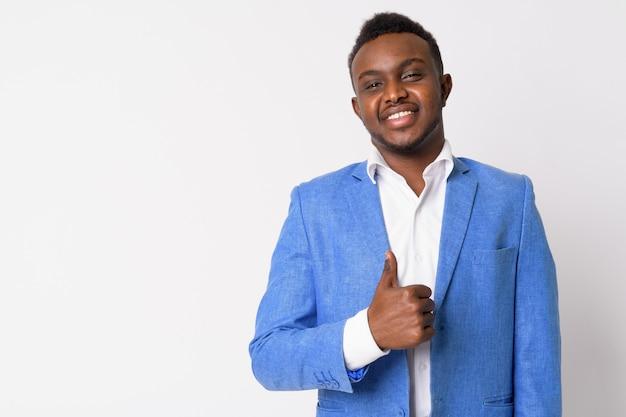 Портрет молодого африканского бизнесмена в синем костюме у белой стены