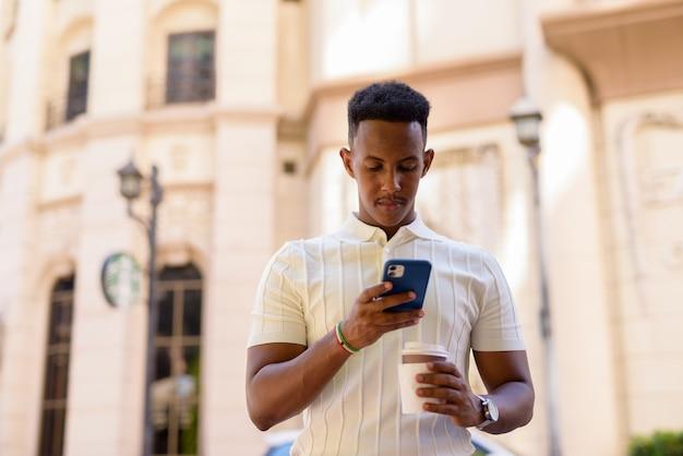 携帯電話でテキストメッセージを送信し、持ち帰り用のコーヒーカップを保持しながらカジュアルな服を着ている若いアフリカのビジネスマンの肖像画