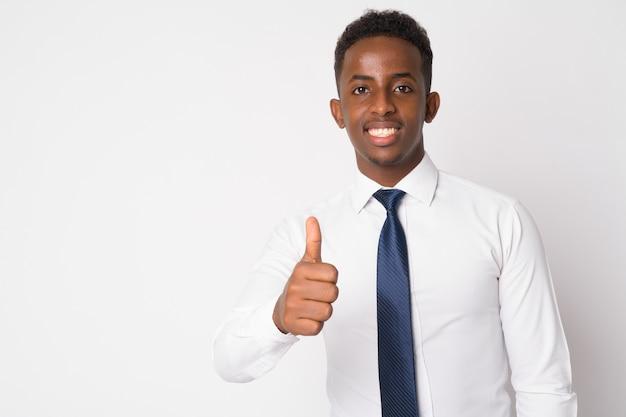 Портрет молодого африканского бизнесмена с афро-волосами на белой стене