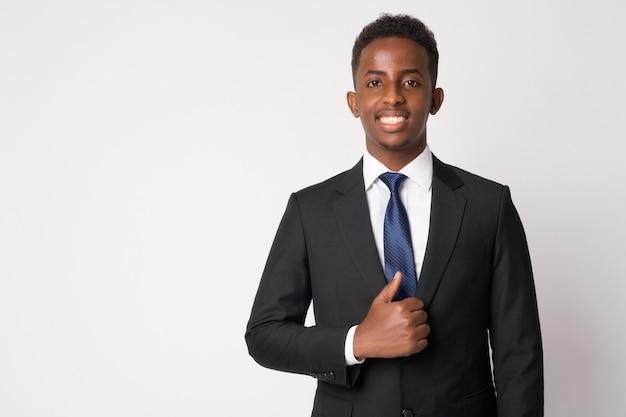 Портрет молодого африканского бизнесмена с афро-волосами в костюме у белой стены