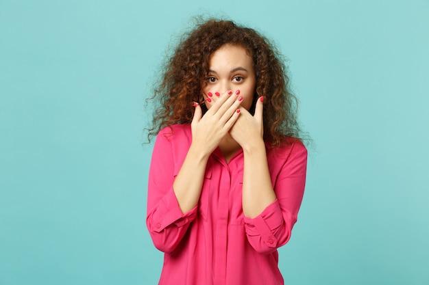 スタジオで青いターコイズブルーの壁の背景に分離された手のひらで口を覆うピンクのカジュアルな服を着た若いアフリカの女の子の肖像画。人々の誠実な感情、ライフスタイルのコンセプト。コピースペースをモックアップします。
