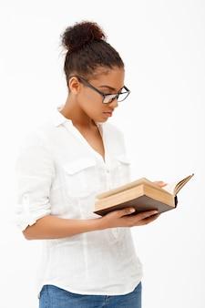 白い壁の上の本を持つアフリカ少女の肖像画