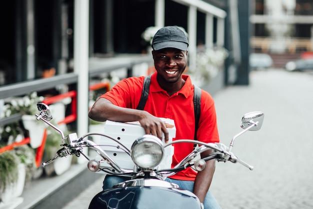 ピザと箱を保持し、彼の自転車に座っているバイクの若いアフリカ人の肖像画。ファーストフードのコンセプト。