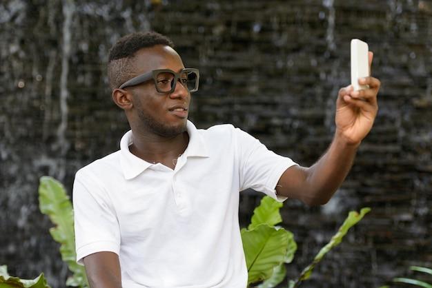 屋外の自然の庭の眺めに対する若いアフリカ人の肖像画