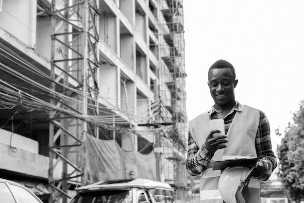 흑인과 백인 야외에서 건물 사이트에서 젊은 아프리카 남자 건설 노동자의 초상화