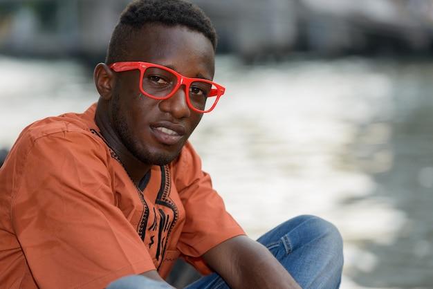 屋外の街の川の景色に対して伝統的な服を着ている若いアフリカ人の肖像画
