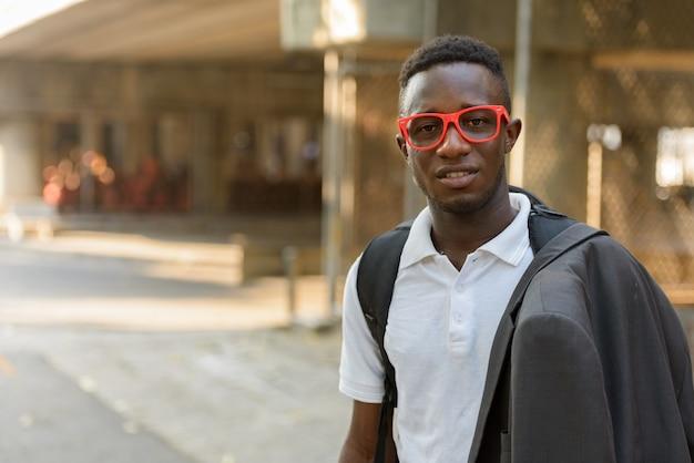 屋外の街の通りで眼鏡をかけた若いアフリカ人の肖像画