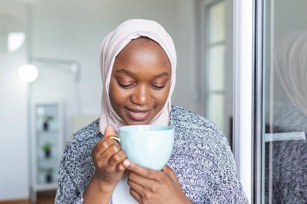 ヘッドスカーフの笑顔で若いアフリカのイスラム教徒の女性の肖像画。東からの真珠。コーヒーマグカップを保持しているヒジャーブを身に着けているイスラム教徒の女性の笑顔。スカーフを身に着けているモダンでスタイリッシュで幸せなイスラム教徒の女性