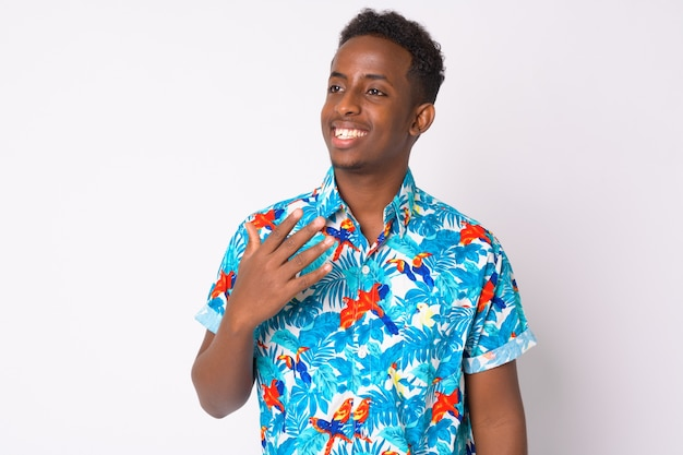 Портрет молодого африканского туриста с афро-волосами на белой стене