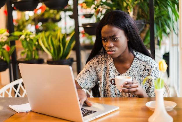 Портрет молодой африканской женщины, пьющей кофе и использующей компьтер-книжку в кафе.