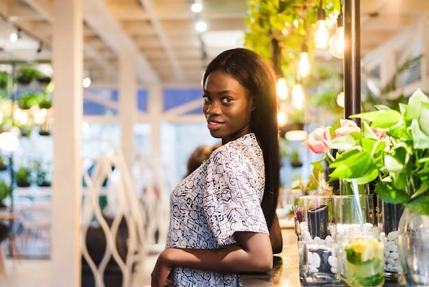 카페에 서있는 젊은 아프리카 여자의 초상화