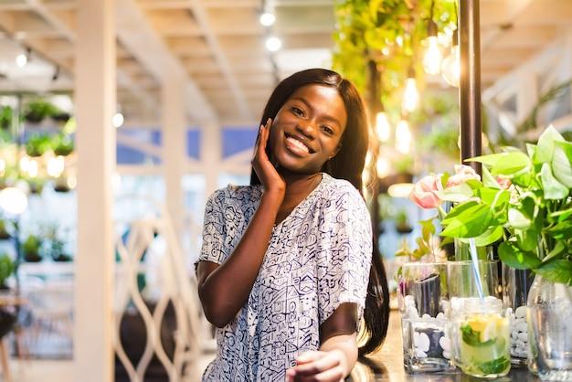 Портрет молодой африканской женщины, стоящей в кафе