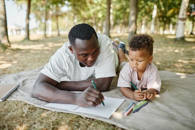 Портрет молодого афроамериканского отца, играющего с милым сыном в парке и рисующего вместе, пока ла ...
