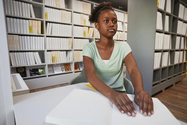 大学図書館のコピースペースで点字本を読んでいる若いアフリカ系アメリカ人女性の肖像画