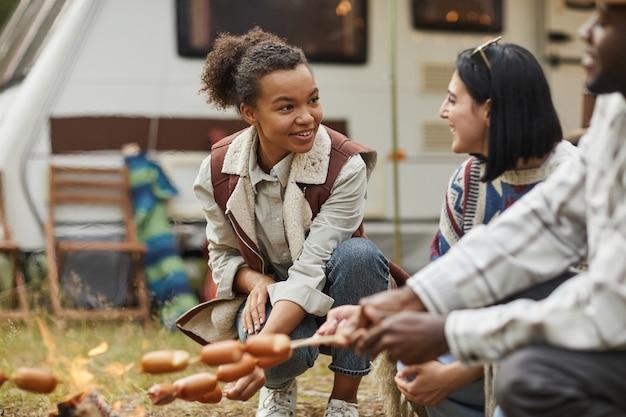 友人とキャンプを楽しみながら火でソーセージを焼く若いアフリカ系アメリカ人女性の肖像画...