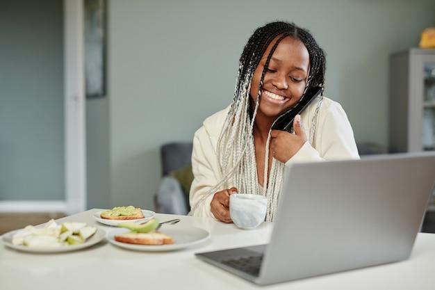 朝の朝食を楽しみながら自宅でビデオチャットを使用して若いアフリカ系アメリカ人女性の肖像画...