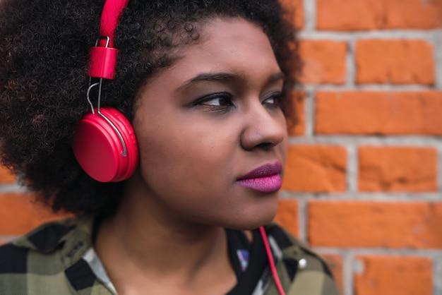 通りでヘッドフォンで音楽を聴く若いアフロアメリカンラテン女性の肖像画。屋外。