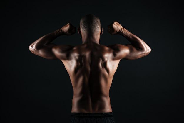 若いアフロアメリカンスポーツの男の肖像、立ちバック、筋肉を示す