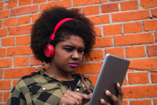 Портрет молодой афро американской женщины используя ее цифровую таблетку с красными наушниками outdoors. концепция технологии.