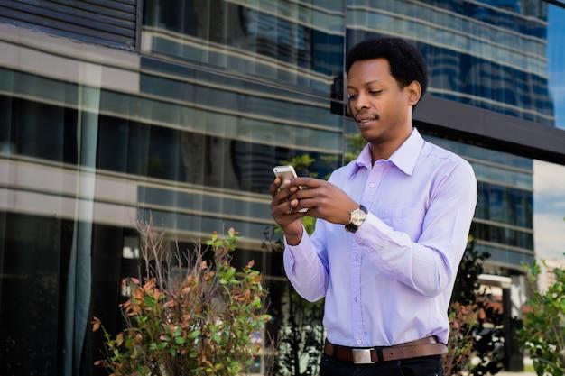 通りで彼の携帯電話を屋外で使用している若いアフロビジネスマンの肖像画。ビジネスコンセプト。