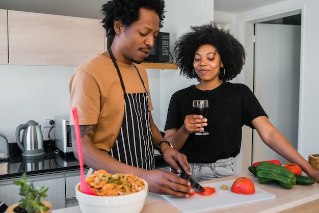 自宅のキッチンで一緒に料理をする若いアフロカップルの肖像画。関係、料理、ライフスタイルのコンセプトです。