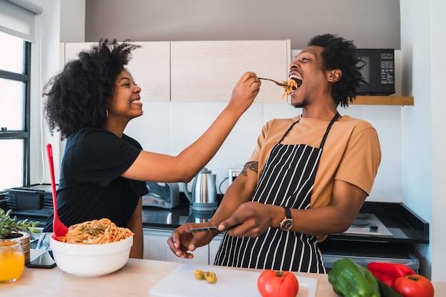 自宅のキッチンで一緒に料理をしている若いアフロカップルの肖像画。関係、料理人、ライフスタイルのコンセプト。