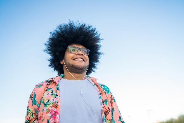 야외 거리에 서있는 동안 이어폰으로 젊은 아프리카 라틴 남자 듣는 음악의 초상화. 도시 개념.