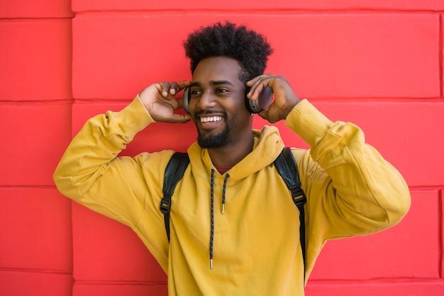 赤い背景にヘッドフォンで音楽を聴いている若いアフロマンの肖像画。技術コンセプト。
