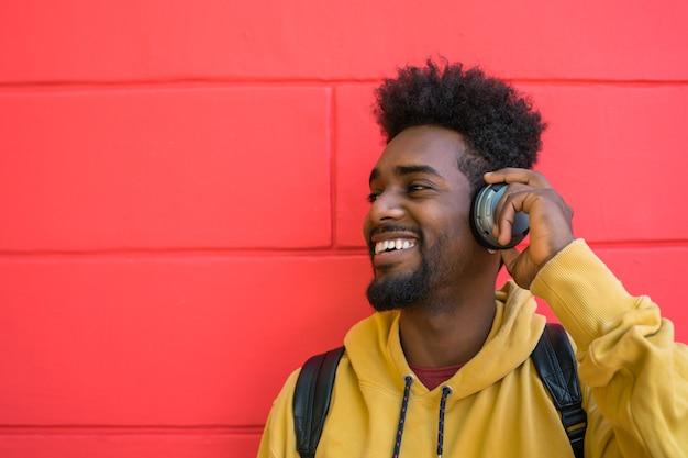 ヘッドフォンで音楽を聴いている若いアフロマンの肖像画