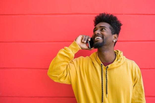 Портрет молодого афро-мужчины разговаривает по телефону у красной стены