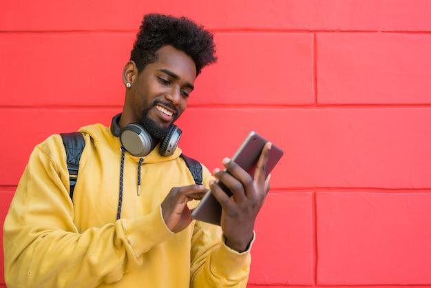 赤い壁にイヤホン付きの彼のデジタルタブレットを使用して若いアフロマンの肖像画。テクノロジーと都市のコンセプト。