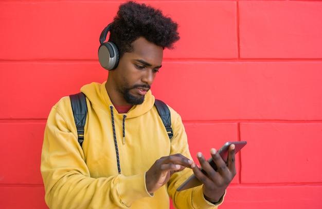 赤い壁にヘッドフォンで彼のデジタルタブレットを使用して若いアフロマンの肖像画。テクノロジーと都市のコンセプト。