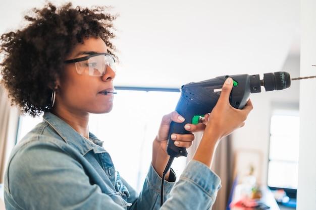 自宅で電気ドリルで壁を掘削する若いアフロ女性の肖像画。ホームセンターのコンセプト。