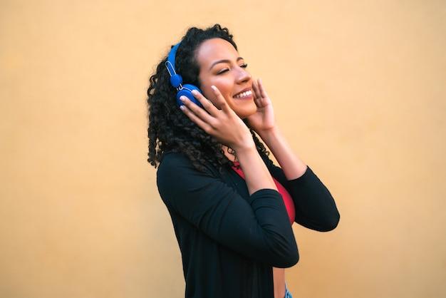 青いヘッドフォンで音楽を楽しんで聞いている若いアフロ女性の肖像画。テクノロジーとライフスタイルのコンセプト。