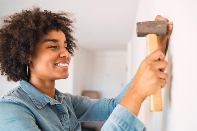 自宅の壁に釘を打つ若いアフロ女性の肖像画