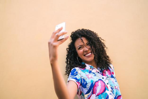 노란색 벽에 그녀의 mophile 전화 selfies를 복용하는 젊은 아프리카 여자의 초상화. 기술 개념.