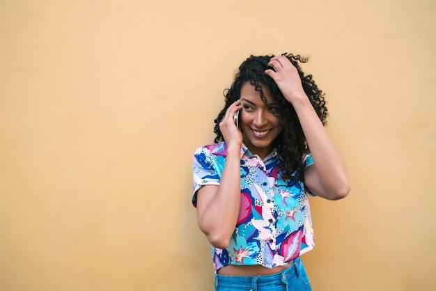 黄色の背景に電話で話している若いアフロ女性の肖像画。コミュニケーションの概念。