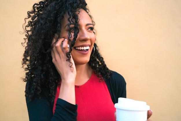 黄色の背景にコーヒーを飲みながら電話で話している若いアフロ女性の肖像画。コミュニケーションの概念。