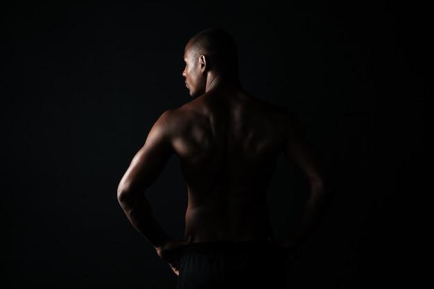 若いアフリカ系アメリカ人のスポーツの男の肖像、後ろに立って、よそ見