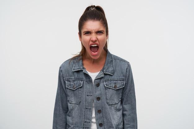 젊은 적극적인 갈색 머리 아가씨의 초상화는 흰색 티셔츠와 데님 재킷을 입고 비명을 지르고 화가 나서, 흰색 배경 위에 선다.