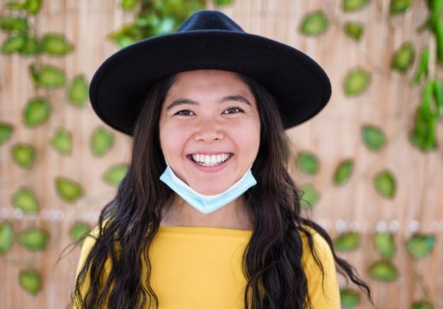 턱 아래 안전 얼굴 마스크를 착용하면서 카메라에 웃는 젊은 aisan 여자의 초상화
