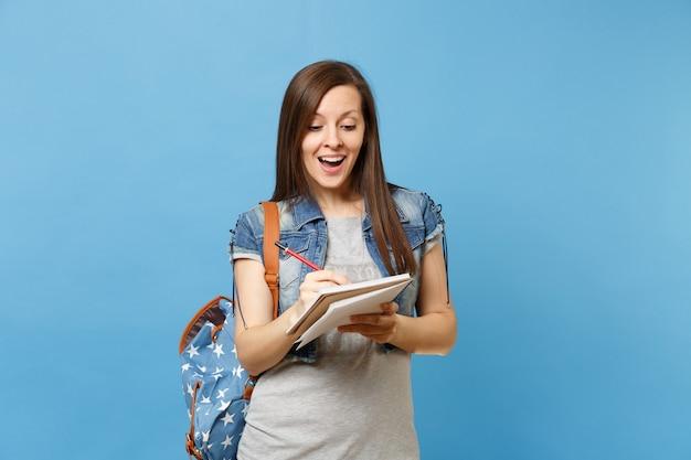파란색 배경에 격리된 노트북에 배낭을 메고 회색 티셔츠를 입은 아름다운 여학생의 초상화. 고등학교 대학 대학 개념의 교육입니다.