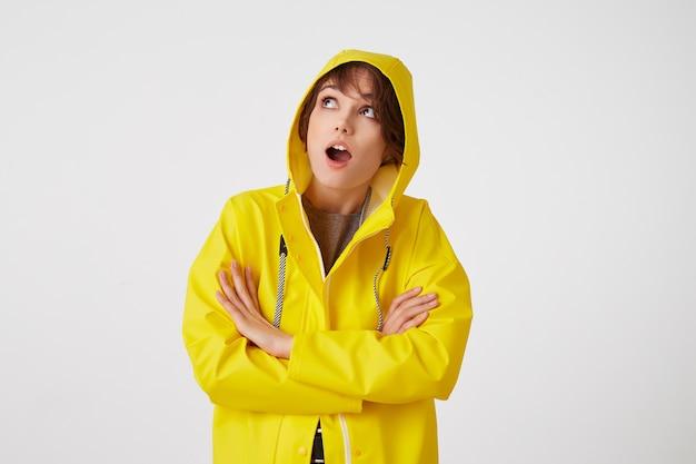 黄色いレインコートを着た若い驚いたかわいい短い髪の少女の肖像画は、大きく開いた口と目で、雨のフードの下に隠れて、腕を組んで白い壁の上に立っています。