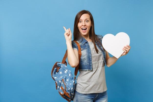 파란색 배경에 격리된 검지 손가락을 가리키는 복사 공간이 있는 흰색 심장을 들고 배낭을 메고 놀란 젊은 여학생의 초상화. 대학에서 교육입니다. 광고 공간을 복사합니다.